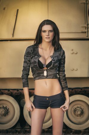 Beautiful sexy young woman beside army tank photo