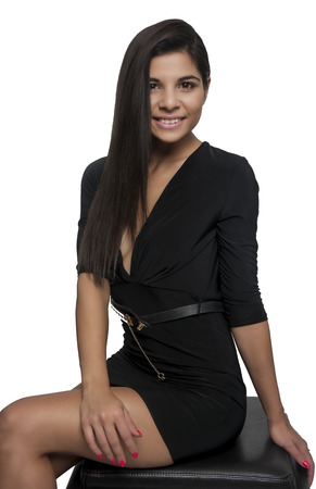 Beautiful young woman wearing black dress sitting isolated against white background photo