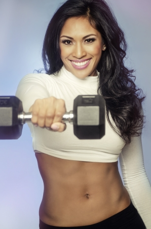 Beautiful smiling happy woman lifting weights photo
