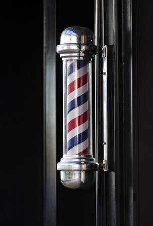 Mens barber hair dressing shop traditional outdoor pole sign helical stripe photo