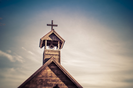 worship white: Old church steeple with bell - sky background add copy