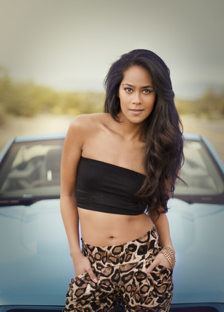 Exotic beautiful young woman beside sports car photo
