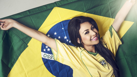 Beautiful happy smiling young woman holding Brazil flag photo