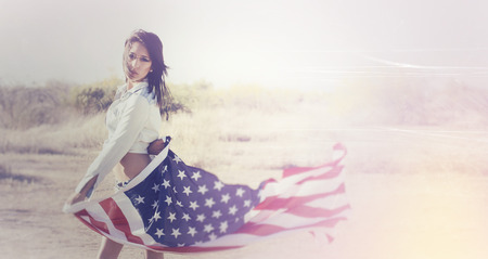 Beautiful young woman wearing denim shorts and top holding American flag in desert location Stock Photo - 27824996