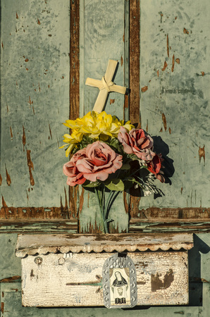 tuscon: Rustic old weathered and worn doorway with charming display of flowers and cross Stock Photo