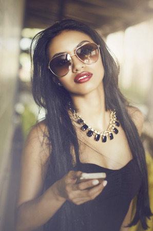 Beautiful young woman holding cell phone