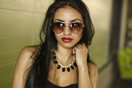 Beautiful face of exotic young woman wearing sunglasses photo