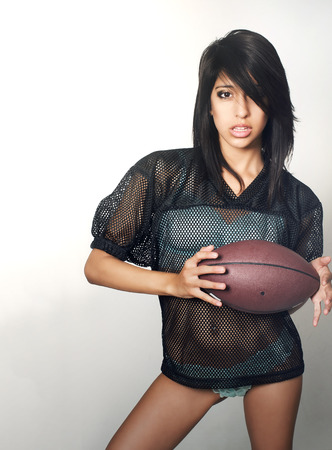 bowl game: Beautiful young woman holding football