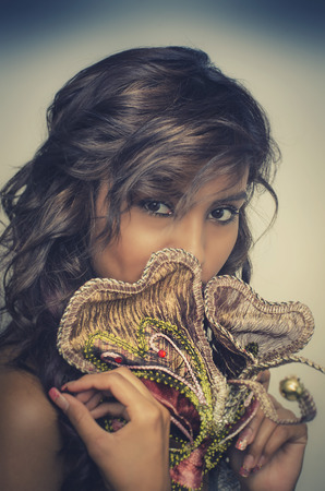 Mysterious beautiful young woman wearing Mardi gras or Venitian mask