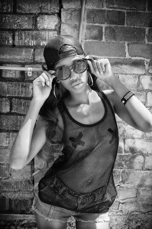 Woman wearing baseball cap, mesh top, sunglasses - city urban vice graffiti wall background photo