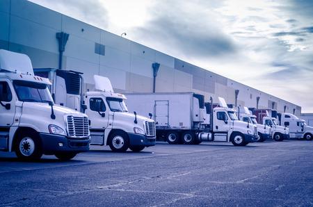 Trucks vrachtwagens laden lossen depot magazijn Stockfoto