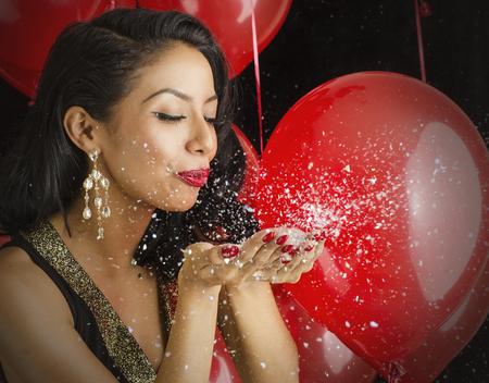 Beautiful young woman blowing confetti photo