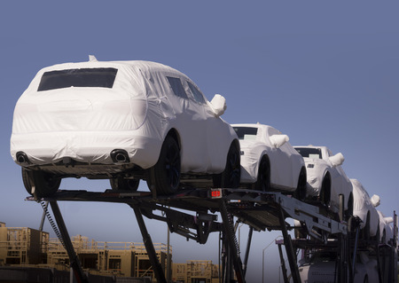 auto dealership: New auto cars under wraps being delivered on truck