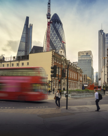 London street scene with iconic red double decker bus commuting workers employees into the City Financial area,.