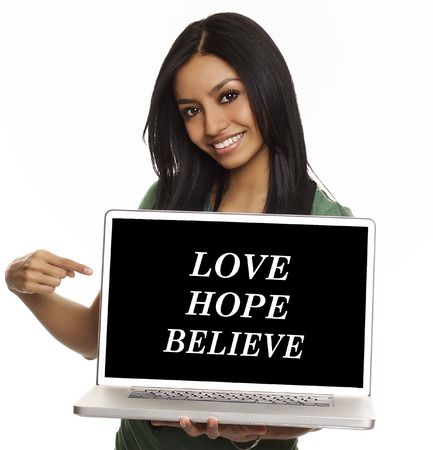 relieved: Pretty young woman pointing to inspiring aspirational message on laptop computer: Love,Hope,Believe. Stock Photo