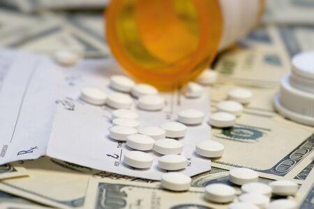 Bottle of prescription pills over dollar bills. 免版税图像 - 43210597