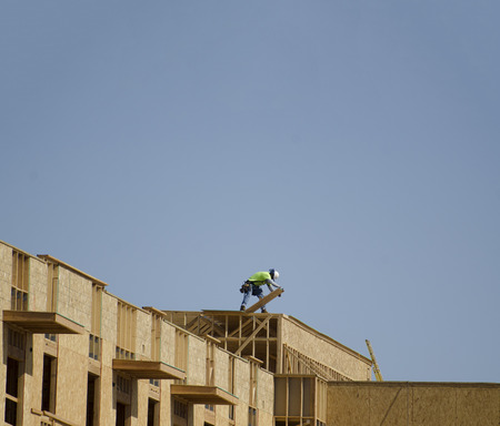 construction crew: Construction crew working on the roof sheeting of  commercial apartment building