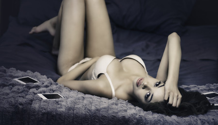 Beautiful exotic young woman lying on bed Stock Photo