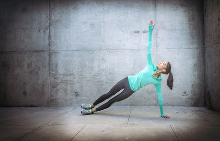 Young woman performing core crunch exercise gritty urban outdoor location Stock Photo