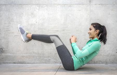 fortaleza: Mujer joven que hace ejercicio contracción del núcleo de realizar arenosa lugar al aire libre urbana