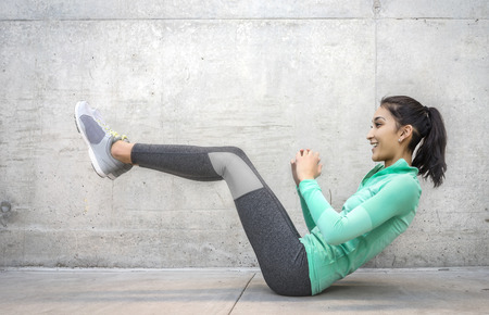 gritty: Young woman performing core crunch exercise gritty urban outdoor location Stock Photo