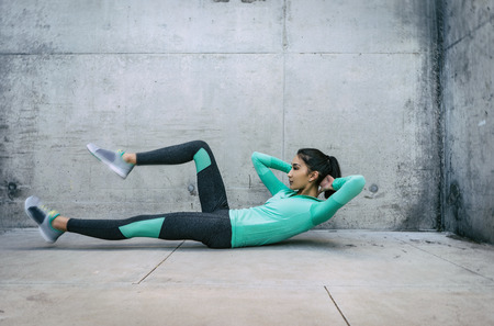 Young woman performing core crunch exercise gritty urban outdoor location Foto de archivo
