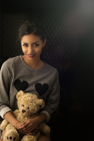 cuddly toy: Beautiful young woman holding toy cuddly bear Stock Photo