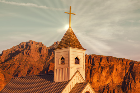 religious building: Sun rays bisecting church steeple of traditional American religious wood architectural worshiping building