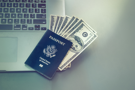 american downloads: Booking travel option abroad online concept image. Passport with American dollars onto of laptop computer.