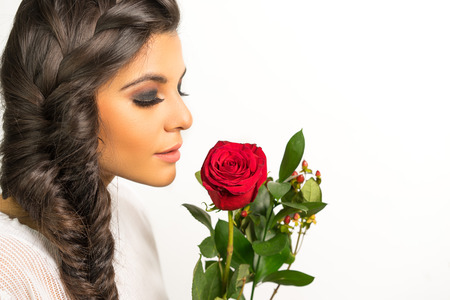 beautiful rose: Beautiful young woman with long braided hair holding red rose Stock Photo