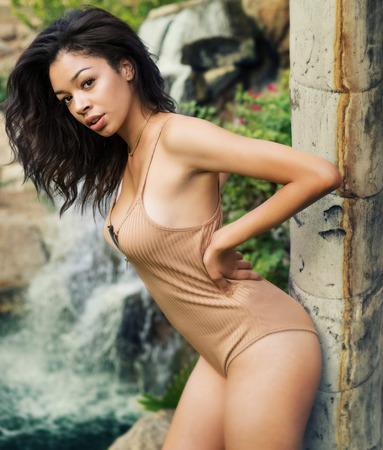 femme brune sexy: Belle jeune femme exotique dans un endroit tropical maillots de bain avec cascade