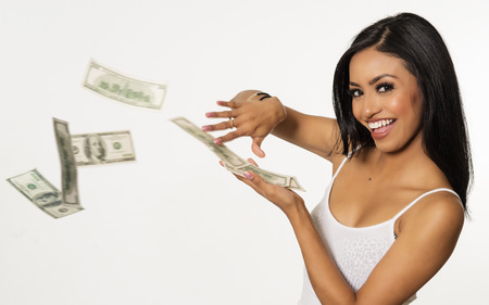 Happy beautiful young woman throwing money