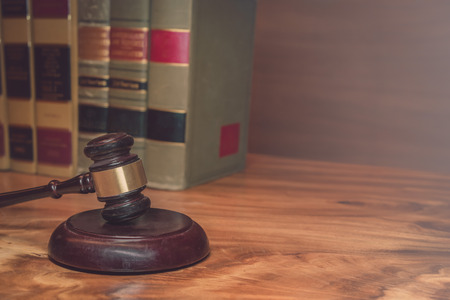 Burden of proof - legal law concept image with Scales of justice and row of law books in background. Hazy light from right good for text copy. Stock Photo