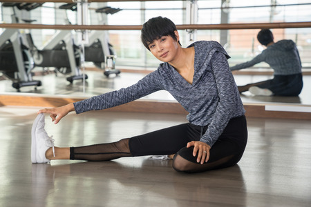 cuerpo femenino: Young woman stretching at gym.  Health and fitness concept image