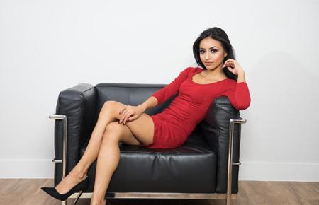 Beautiful woman in red dress sitting on black chair Foto de archivo