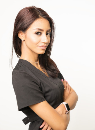 ethnic woman: Attractive woman wearing scrubs for role in multiple career choices such as beautician or care giver. Stock Photo