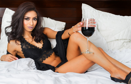 women in underwear: Beautiful woman relaxing with glass of wine in bed Stock Photo