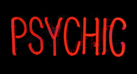 Psychic red neon light sign glowing at night.