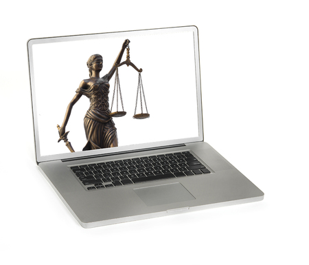 Legal law concept image with Scales of justice displayed on laptop computer