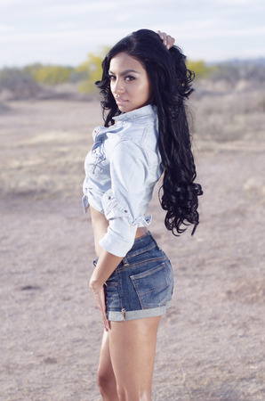 Beautiful woman wearing denim shorts and top outdoors in desert location