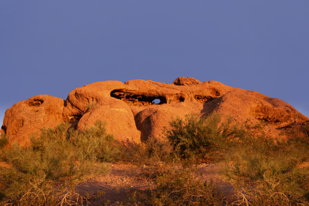 Papago Park known as the hole in the rock glowing red orange as sunsets over Phoenix,Arizona,USA Stock Photo