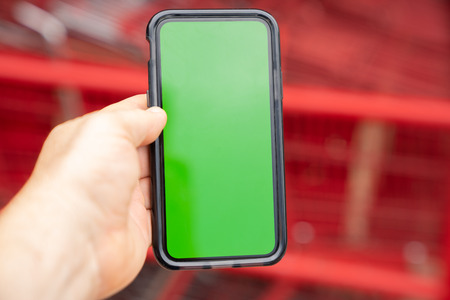 Man holding green screen smart phone with blurred shopping carts in background. Imagens