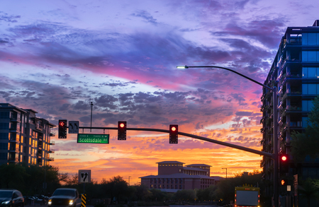 Dramatic sunset in North Scottsdale,Arizona. Cars drive by a busy intersection on Scottsdale rd and Kierland Blvd. Focus on road sign. Imagens