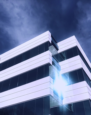 Sun shining on generic modern office window.  Dramatic intense light and blue sky add to the graphic business stylistic image