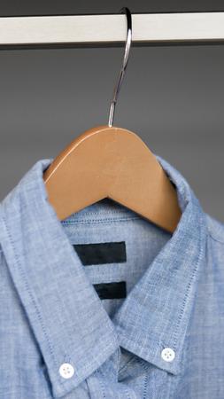 Mens blue button up shirt hanging in closet, denim Imagens - 117287962