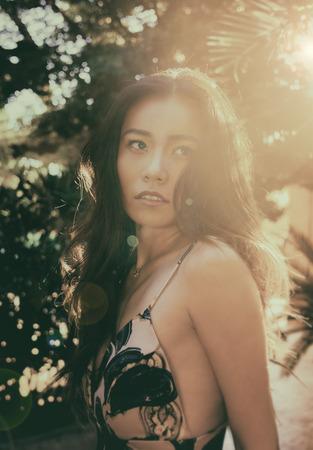 Beautiful luxury woman wearing summer dress in tropical location looking back Imagens