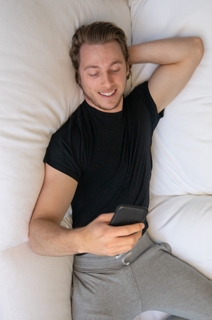 Smiling man looking at mobile cell phone while texting or face timing during call Imagens - 121649806