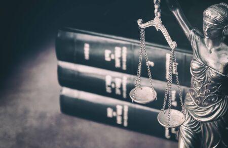 Balanza de la justicia con libros de derecho en segundo plano.