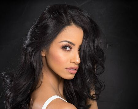 Le visage de la belle jeune femme avec de magnifiques cheveux noirs bouclés