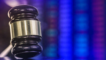 Legal law concept image gavel with financial data on computer monitor.